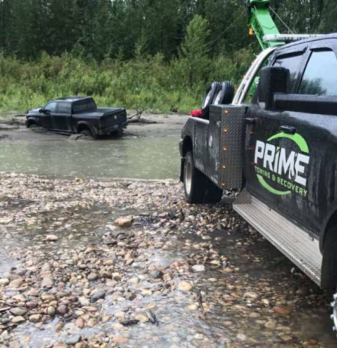 Prime Tow Truck Rescuing a Truck Out of a River Near Grande Prairie, AB